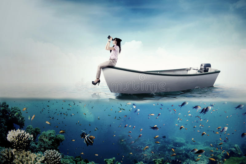 Businesswoman with binoculars on boat. Young businesswoman sitting on the boat while looking forward through binoculars at the sea royalty free stock photography