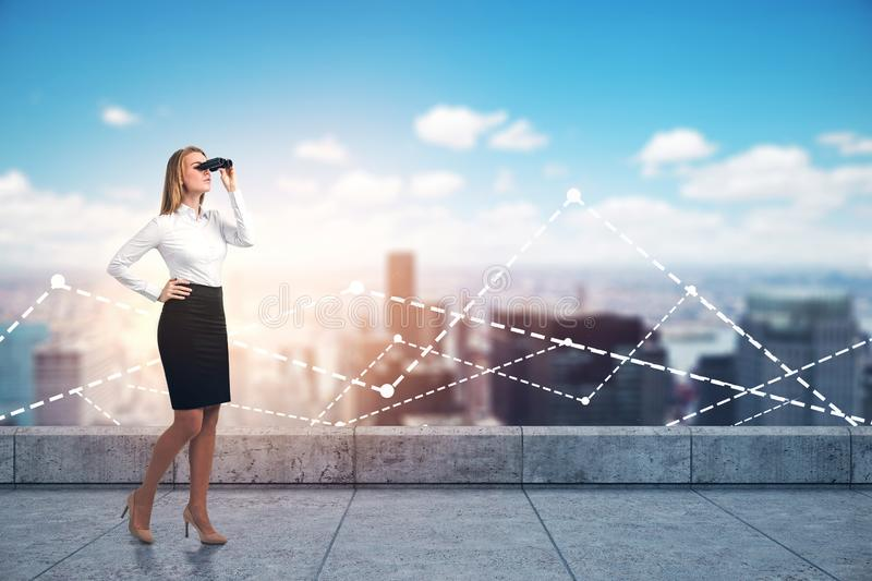 Businesswoman with binoculars on city roof, graphs stock image