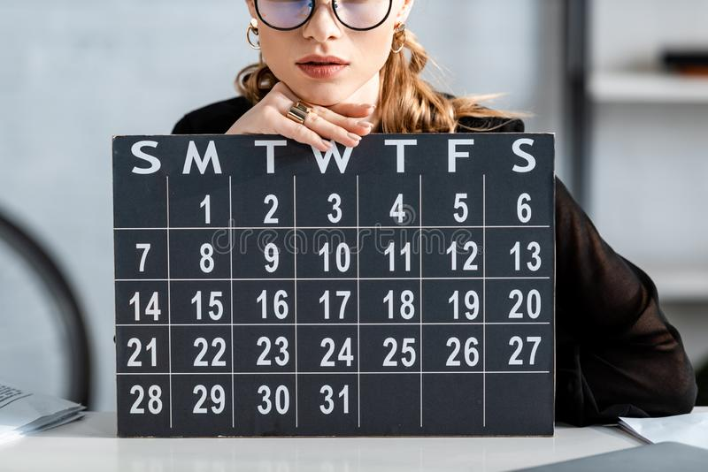 Businesswoman in black clothes and glasses. Holding calendar stock image