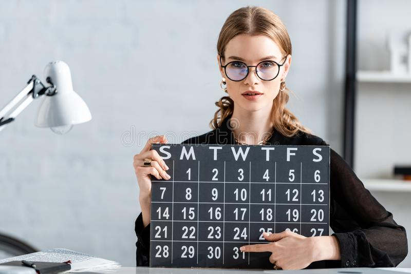 Businesswoman in black clothes and glasses holding calendar and sitting. On chair stock images