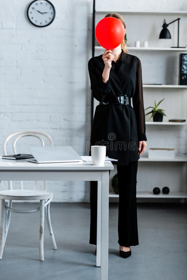 Businesswoman in black clothes. Hiding face behind red balloon stock photos