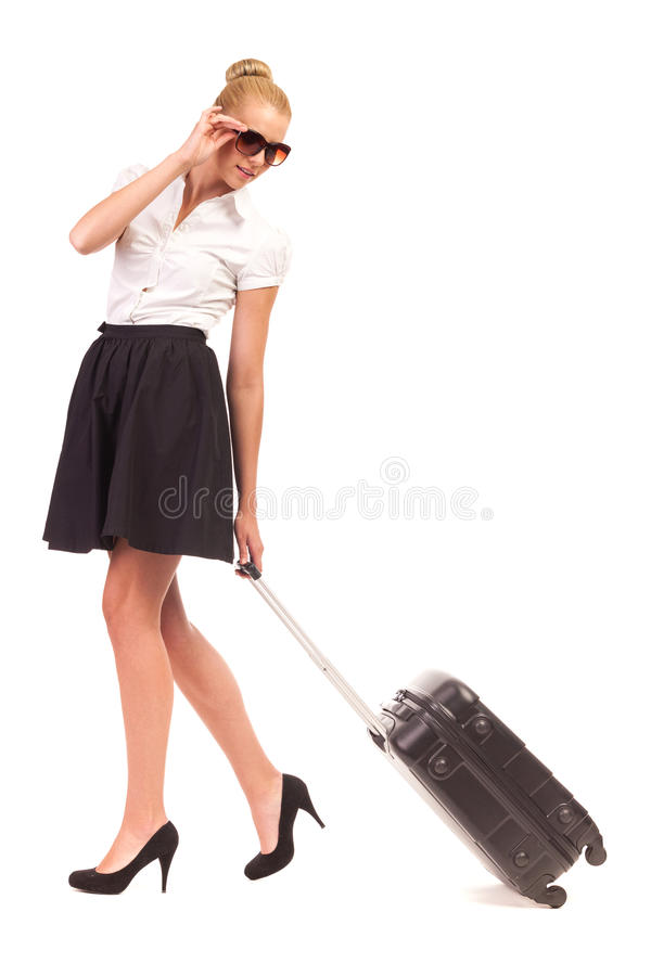 Businesswoman with black suitcase looking back. stock photos