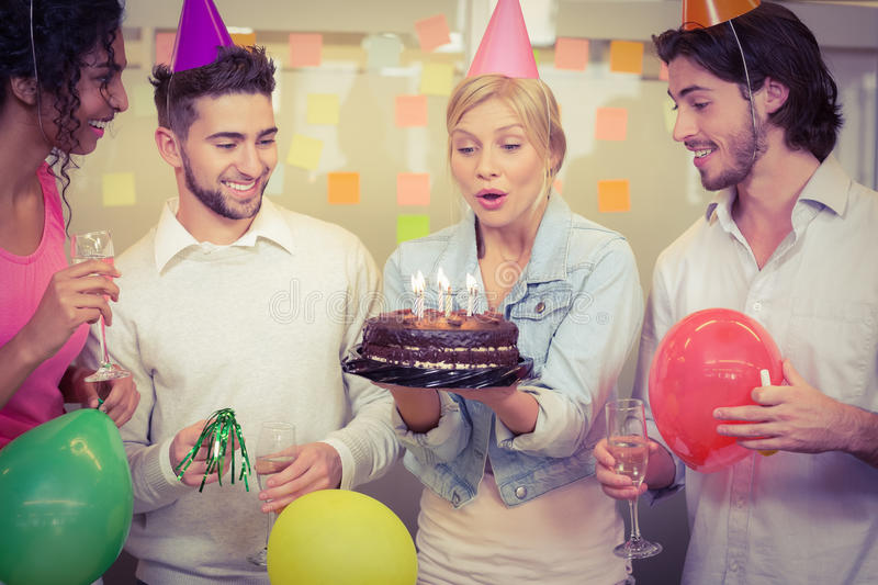 Businesswoman blowing birthday candles royalty free stock photography