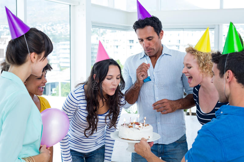 Businesswoman blowing candles on her birthday cake. In the office stock photos