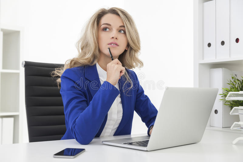 Businesswoman in blue blazer is composing a document. Woman in blue blazer is thinking about the document she is composing. Concept of business people stock image