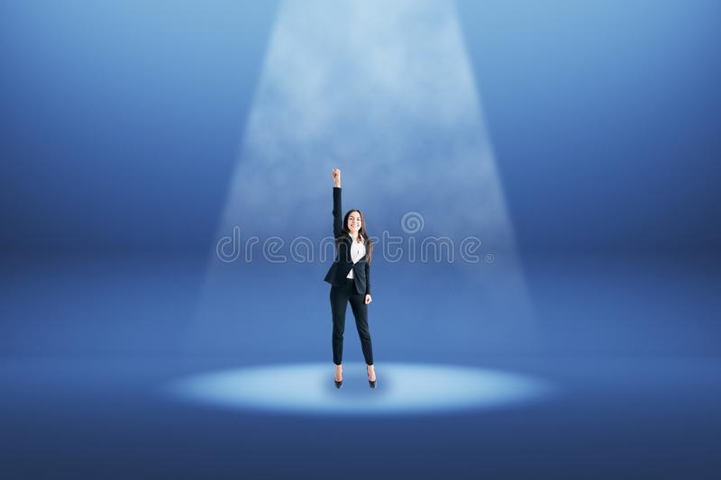 Businesswoman in blue spotlight. Celebrating young businesswoman standing under spotlight on blue background. Best employee concept royalty free stock photo