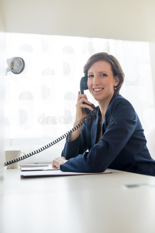Businesswoman in blue suit calling someone through telephone royalty free stock photo