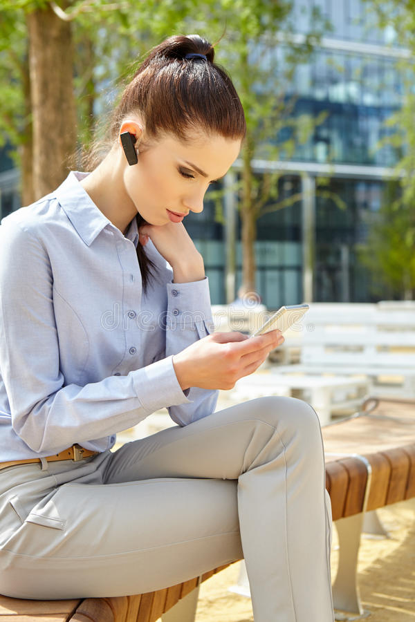 Businesswoman with Bluetooth. Headset phone stock photography