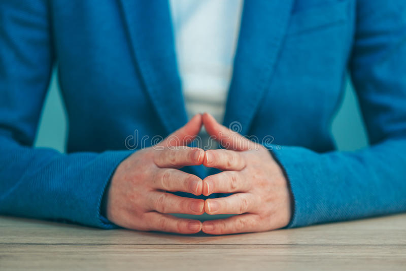 Businesswoman body language for confidence and self-esteem. Hands with steepled fingers on office desk royalty free stock image