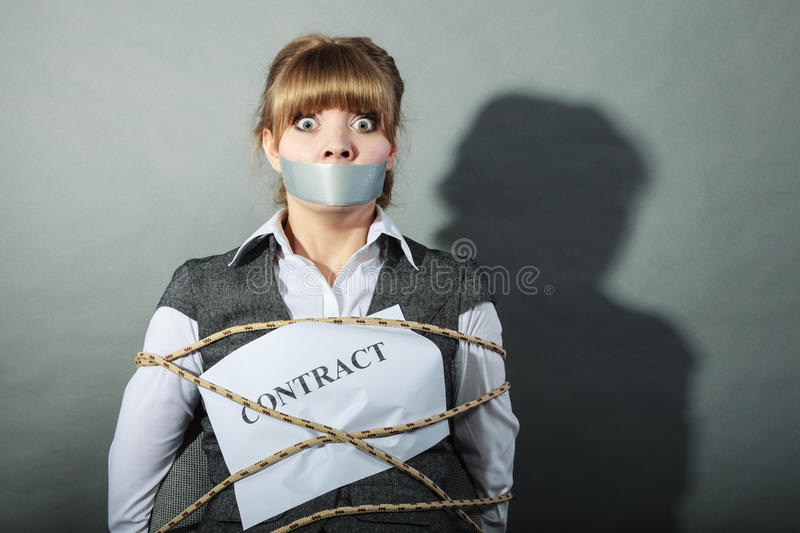 Businesswoman bound by contract with taped mouth. Afraid businesswoman bound by contract terms and conditions with mouth taped shut. Scared woman tied to chair stock photo