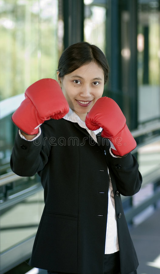 Businesswoman with boxing glove stock images