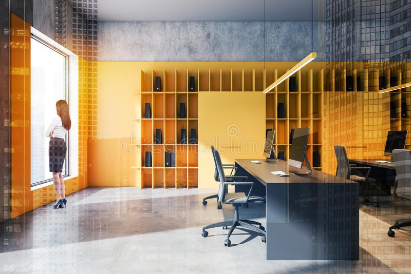 Businesswoman in bright yellow loft office. Young businesswoman looking in the window of modern loft office with yellow and concrete walls and rows of computer stock image