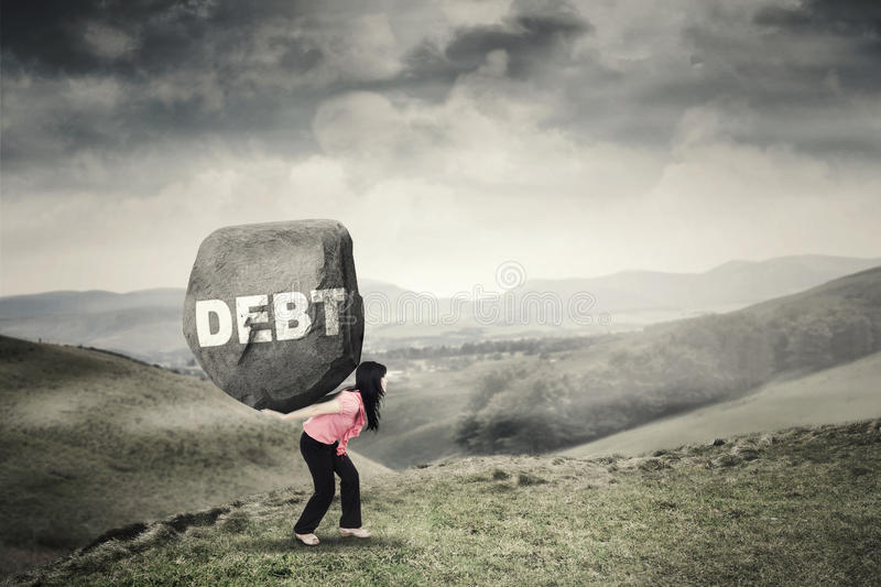 Businesswoman brings rock with Debt word. Picture of a businesswoman walking on the mountain while brings a big rock with Debt word on her back stock photos
