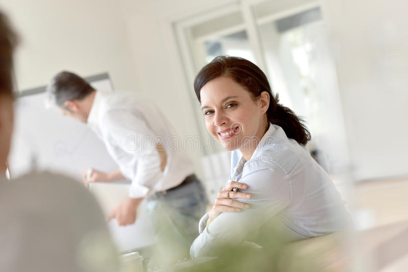 Businesswoman in business conference. Portrait of smiling businesswoman attending marketing presentation royalty free stock image