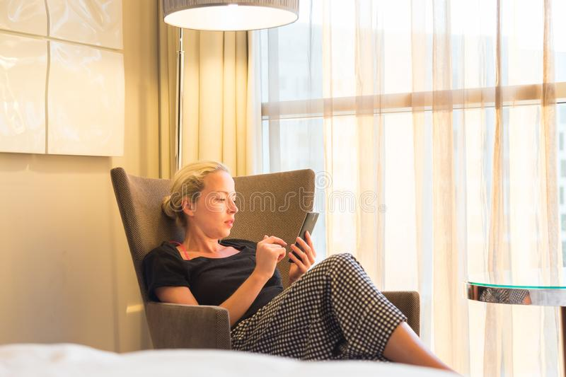 Businesswoman on business travel, tired from business meeting, sitting alone in hotel room afterwork, reading and royalty free stock photos