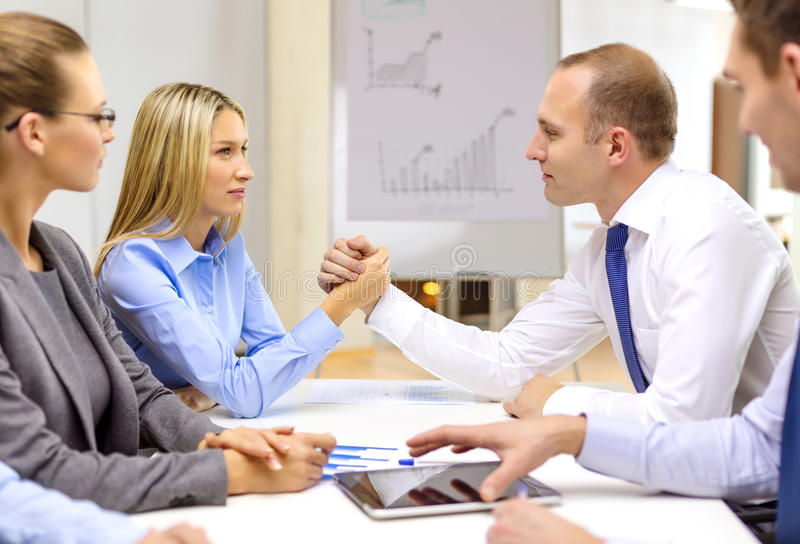 Businesswoman and businessman arm wrestling. Business and office concept - businesswoman and businessman arm wrestling during meeting in office royalty free stock photo