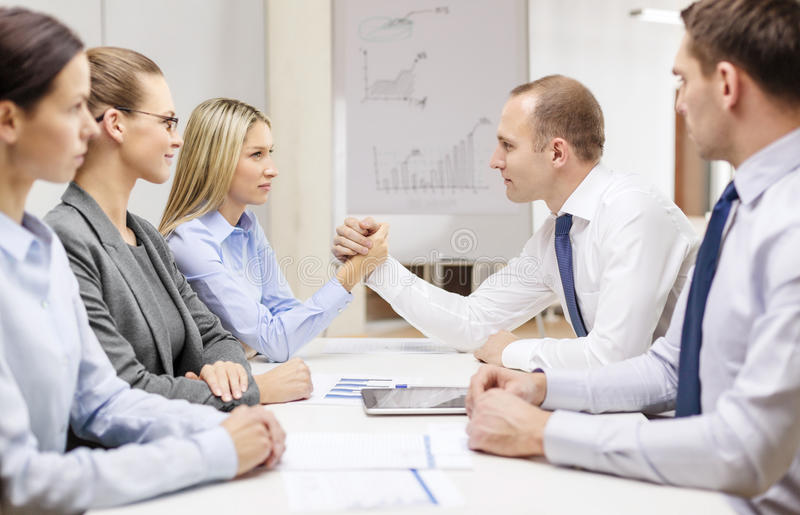 Businesswoman and businessman arm wrestling. Business and office concept - businesswoman and businessman arm wrestling during meeting in office stock image