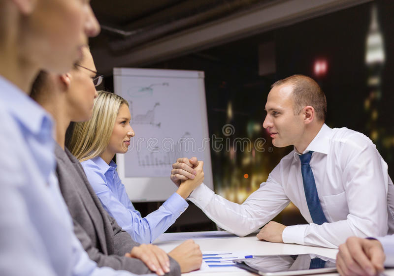 Businesswoman and businessman arm wrestling. Business and office concept - businesswoman and businessman arm wrestling during meeting in office royalty free stock photography