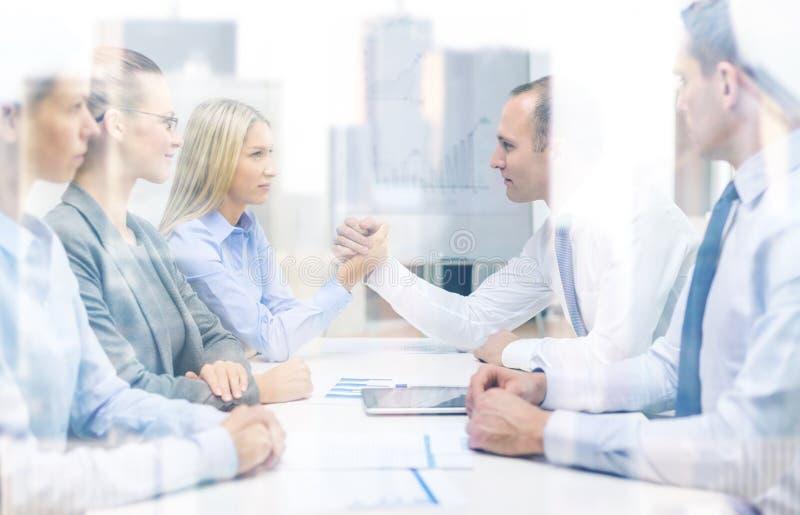 Businesswoman and businessman arm wrestling. Business and office concept - businesswoman and businessman arm wrestling during meeting in office stock photo
