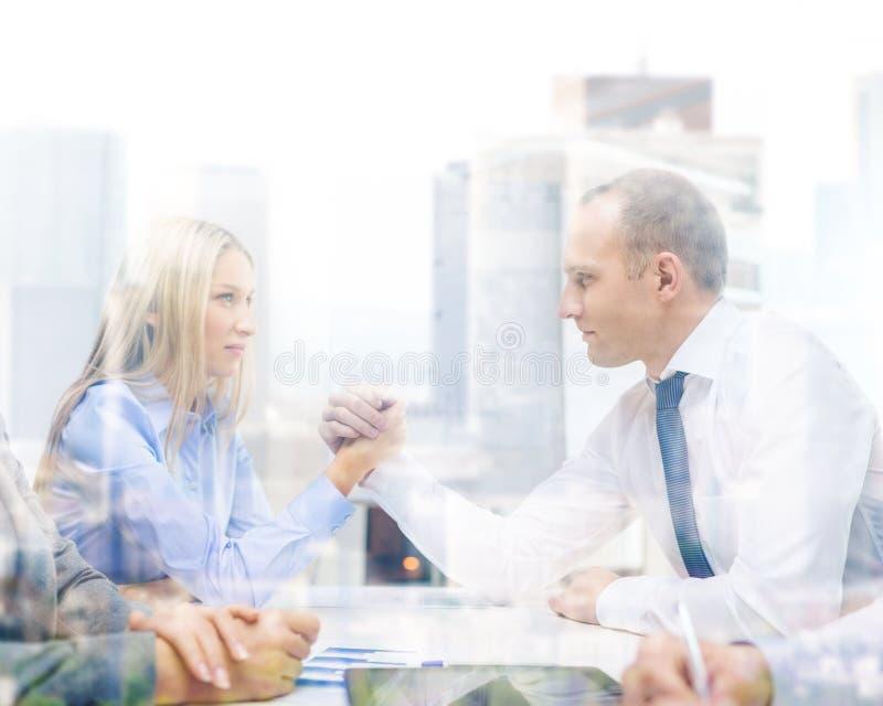 Businesswoman and businessman arm wrestling. Business and office concept - businesswoman and businessman arm wrestling during meeting in office stock photos