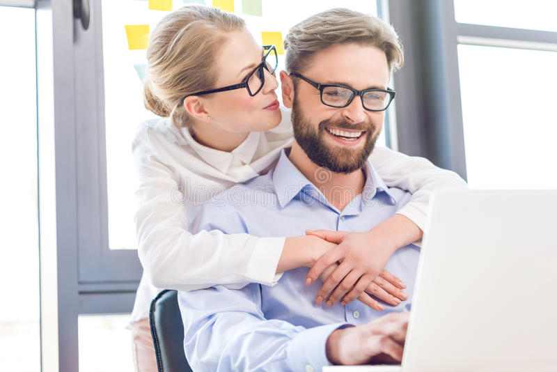Businesswoman and businessman with eyeglasses hugging and working with laptop royalty free stock image