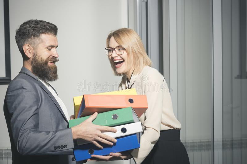 Businesswoman and businessman with folders. Man help woman to carry binders in office. Bearded man and girl with. Businesswoman and businessman with folders. Man royalty free stock images