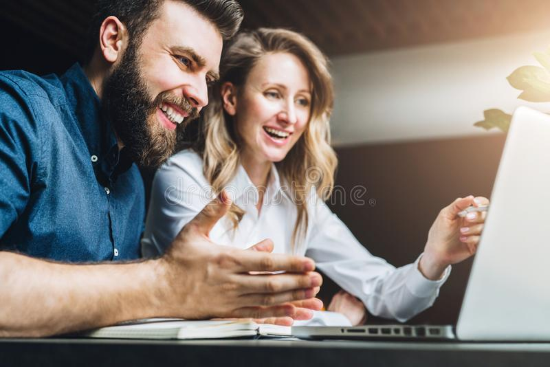 Businesswoman and businessman are sitting at desk against laptop and discussing business project, working together. royalty free stock images