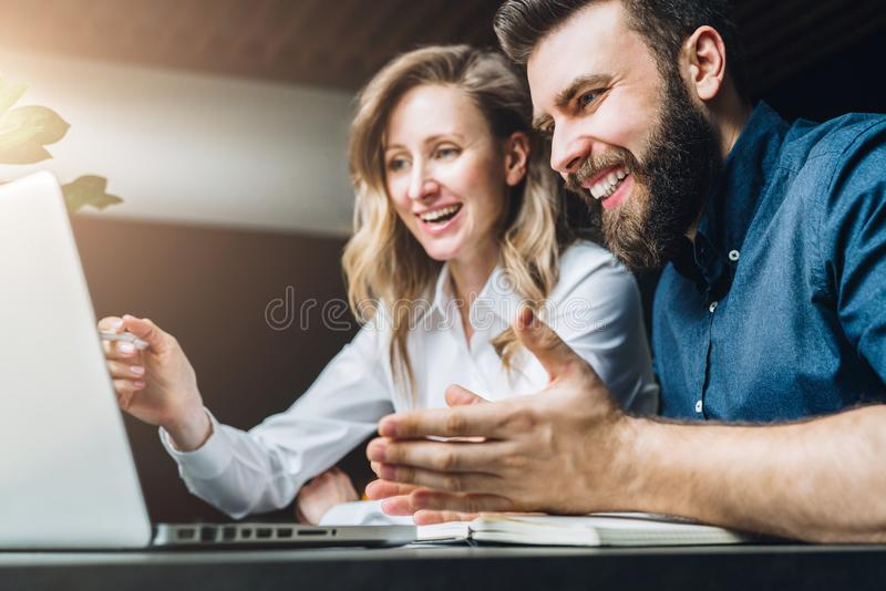 Businesswoman and businessman are sitting at desk against laptop and discussing business project, working together. Teamwork. Businesswoman and businessman are royalty free stock images