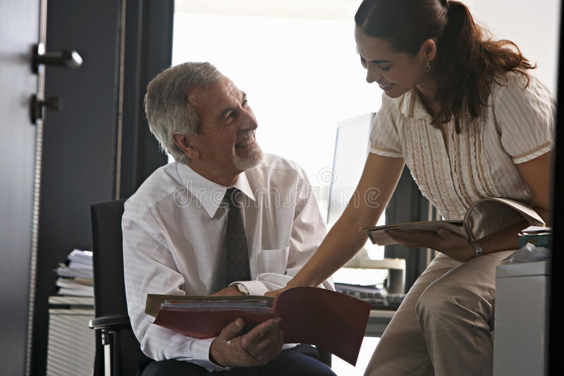 Businesswoman and businessman talking in office, looking at file, smiling royalty free stock photography