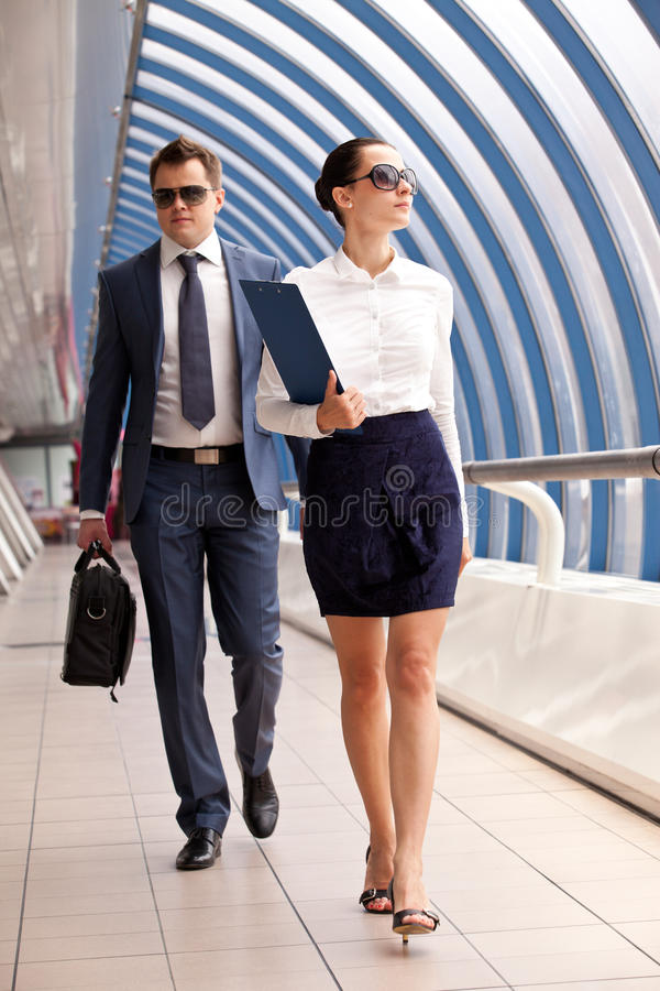 Businesswoman and businessman. Walk down the hall in the business center stock photography