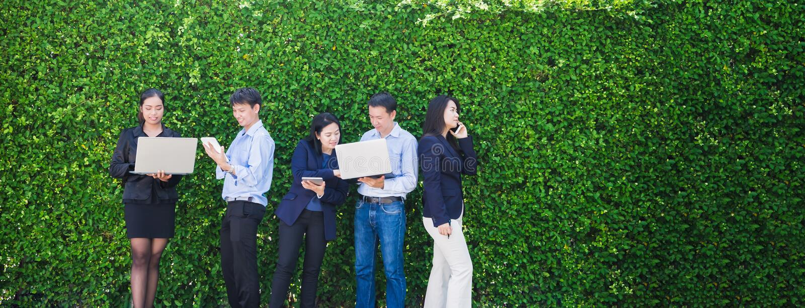 Businesswoman and businessman working outside office using lapto stock images