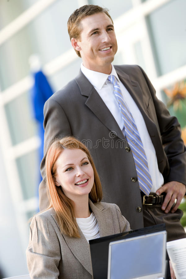 Businesswoman and businessman working at pavement cafe table, smiling (tilt) stock images