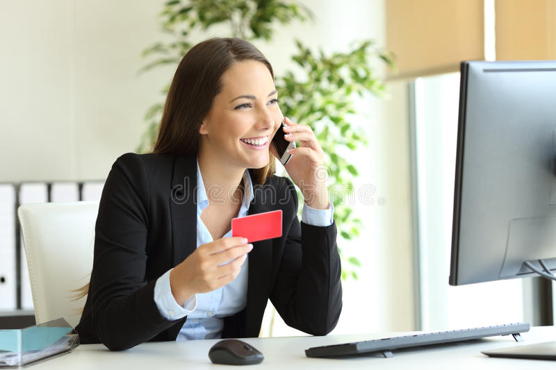 Businesswoman buying online and calling customer service stock image