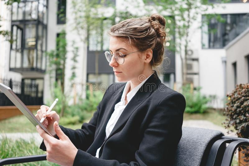 Young business woman sitting at coffee shop working on digital tablet. Businesswoman at cafe on veranda using gadgets for digital work. Young business woman royalty free stock image