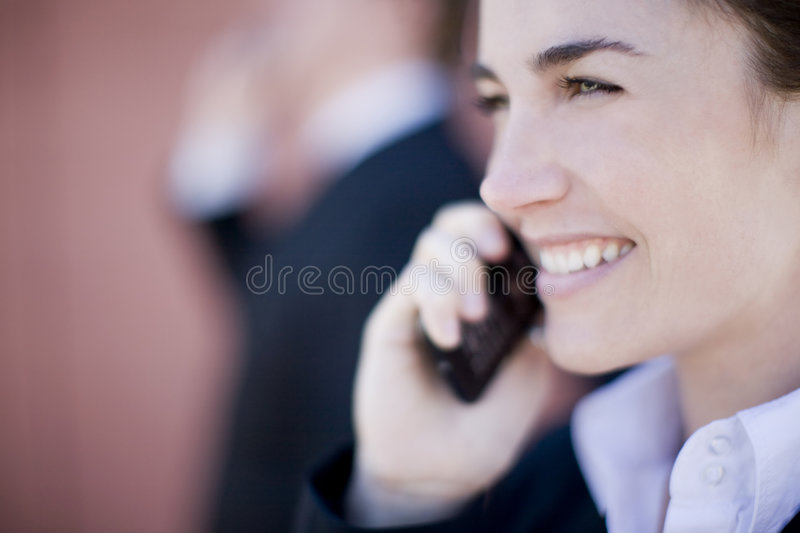Businesswoman call. Close view of businesswoman smiling with cellphone next to face royalty free stock photography