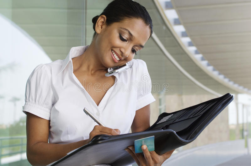 Businesswoman On Call While Writing Notes stock images