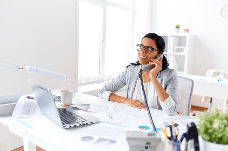 Businesswoman calling on desk phone at office royalty free stock photography