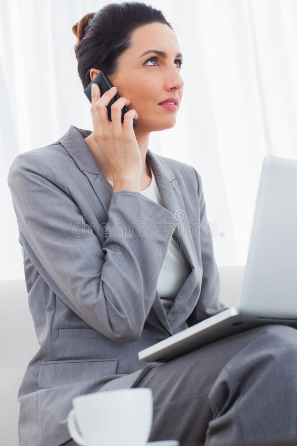 Businesswoman Calling With Her Mobile Phone And Using Laptop Sit Royalty Free Stock Photography