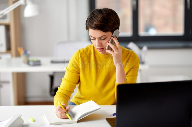 Businesswoman calling on smartphone at office royalty free stock image