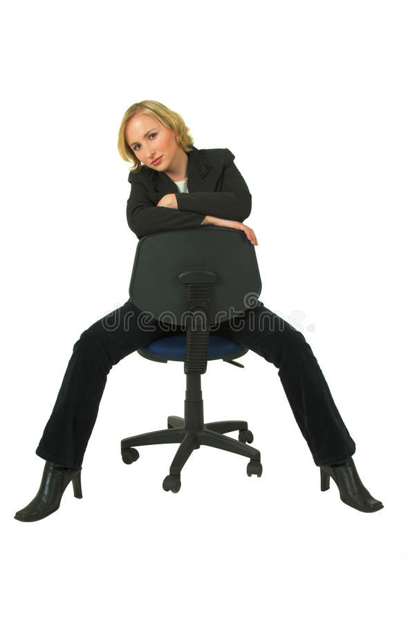 Businesswoman on chair. Fashionable young businesswoman in black suit sat leaning over back of office chair; white studio background royalty free stock photos