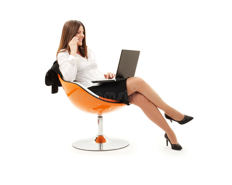 Businesswoman in chair with laptop and phone royalty free stock photo