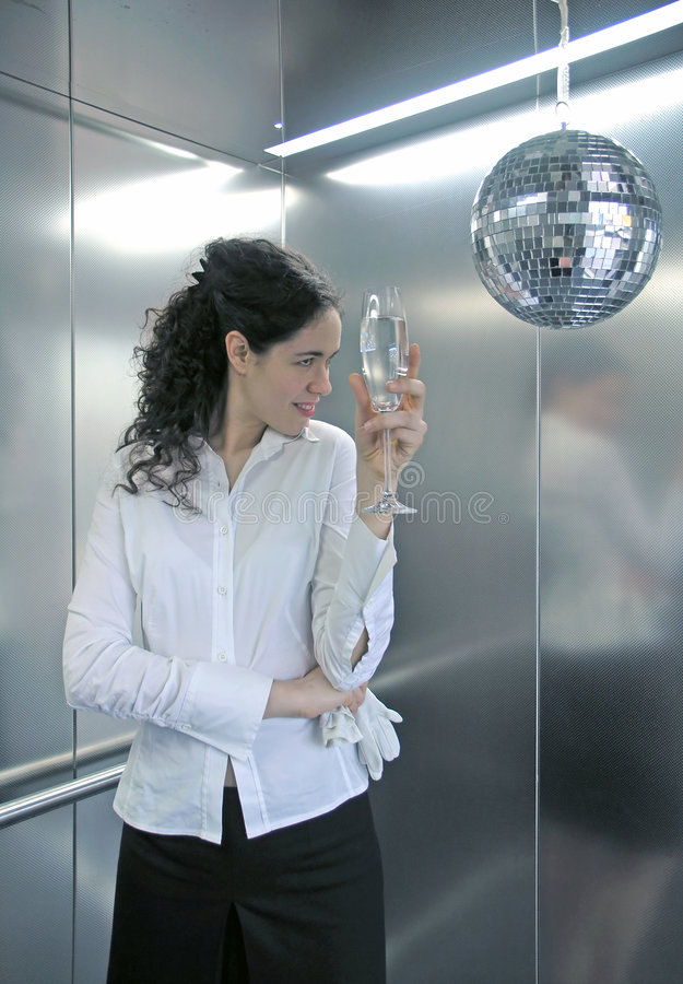 Businesswoman with champagne. Half body portrait of young businesswoman with champagne, silver office walls in background stock image