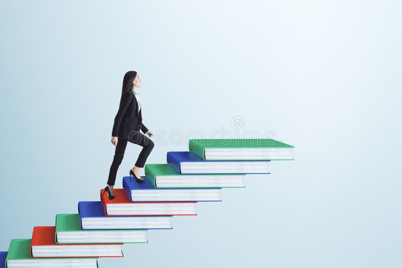 Education and career concept. Businesswoman climbing book pile ladder. Sky background. Education and career concept stock image