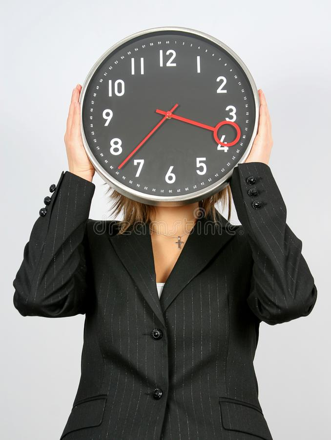 Businesswoman and clock. Young businesswoman with clock covering her head stock photos