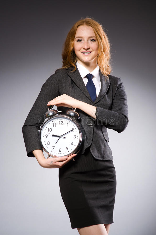 Businesswoman with clock being late stock photo