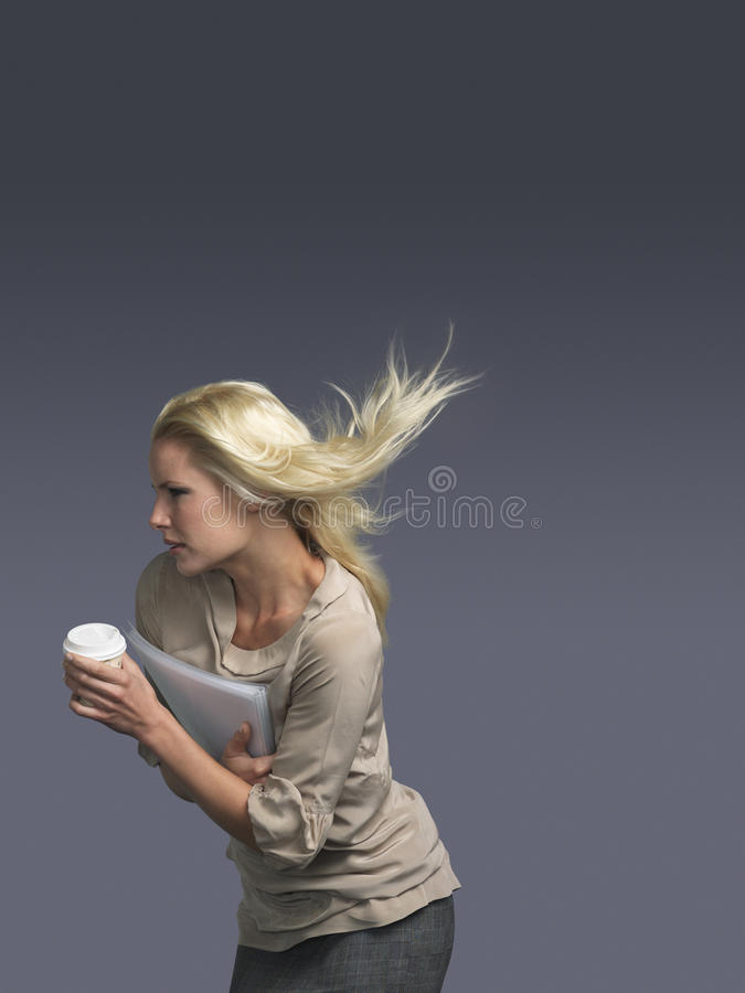 Businesswoman With Coffee Cup And Blond Hair Blowing In Wind royalty free stock photos