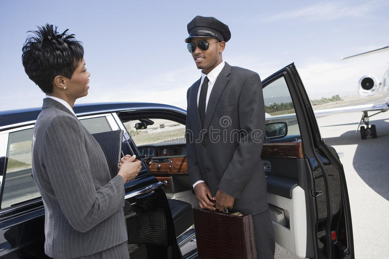 Businesswoman Communicating With Driver On Airfield. An African American business women communicating with driver while standing by car on airfield stock images