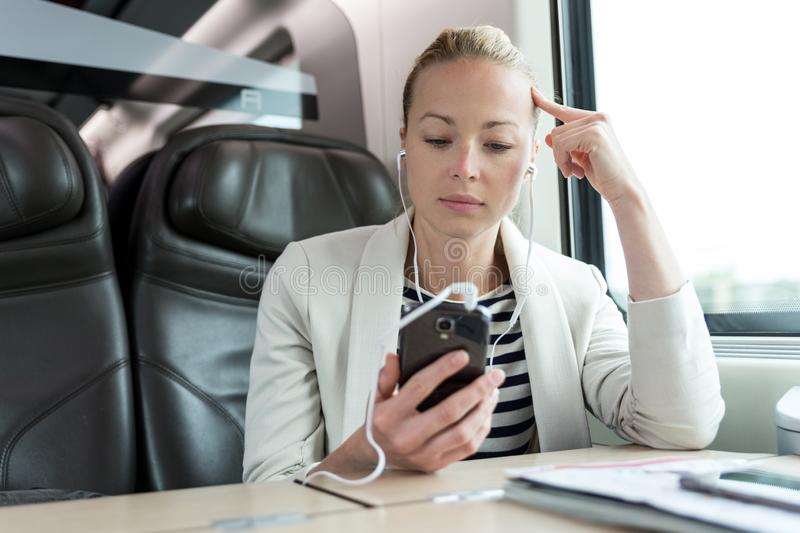 Businesswoman communicating on mobile phone while traveling by train. Businesswoman communicating on cellphone using headphone set while traveling by train in royalty free stock images