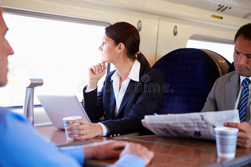 Businesswoman Commuting To Work On Train And Using Laptop stock photography