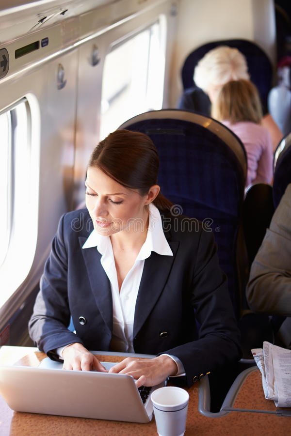 Businesswoman Commuting To Work On Train And Using Laptop stock image